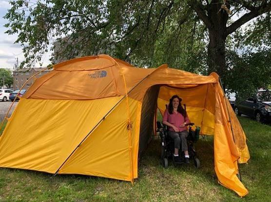 Portrait d'une personne en chaise roulante dans une tente