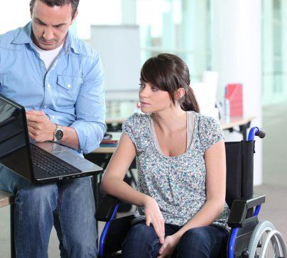 Portrait d'un homme avec un ordinateur portable et femme en chaise roulante