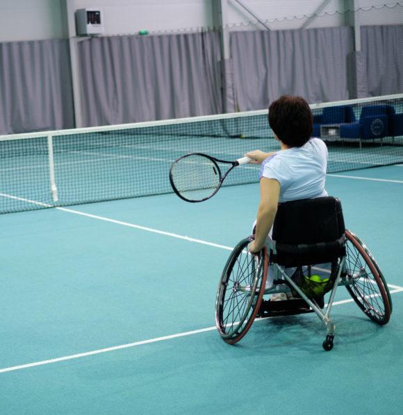 Portrait d'une femme en chaise roulante jouant au tennis