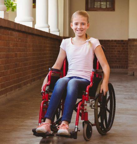 Portrait d'une jeune fille souriante en chaise roulante