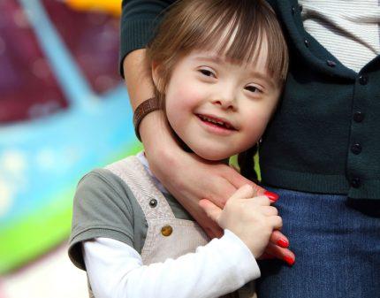 Portrait d'une enfant souriante entourée du bras de son accompagnatrice