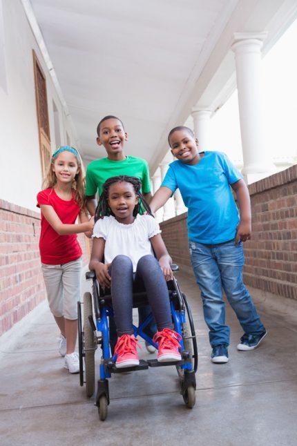 Portrait d'un groupe d'enfants heureux dont un est en chaise roulante