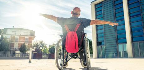 Portrait d'un homme en chaise roulante à l'extérieur mimant un avion